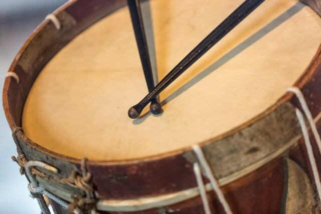 Closeup photo of old military drum with black sticks